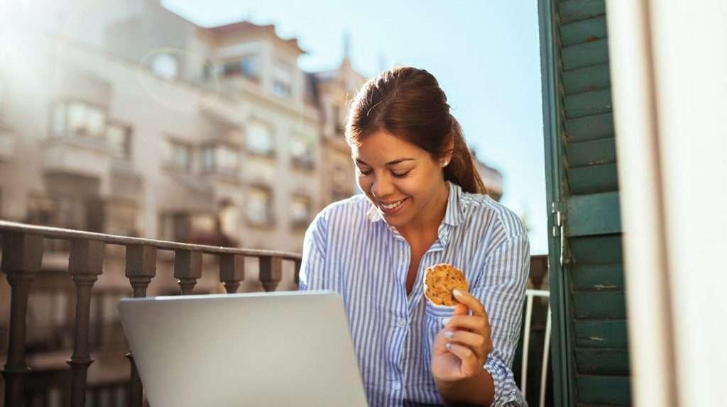 Beautiful woman having snack on a balcony.