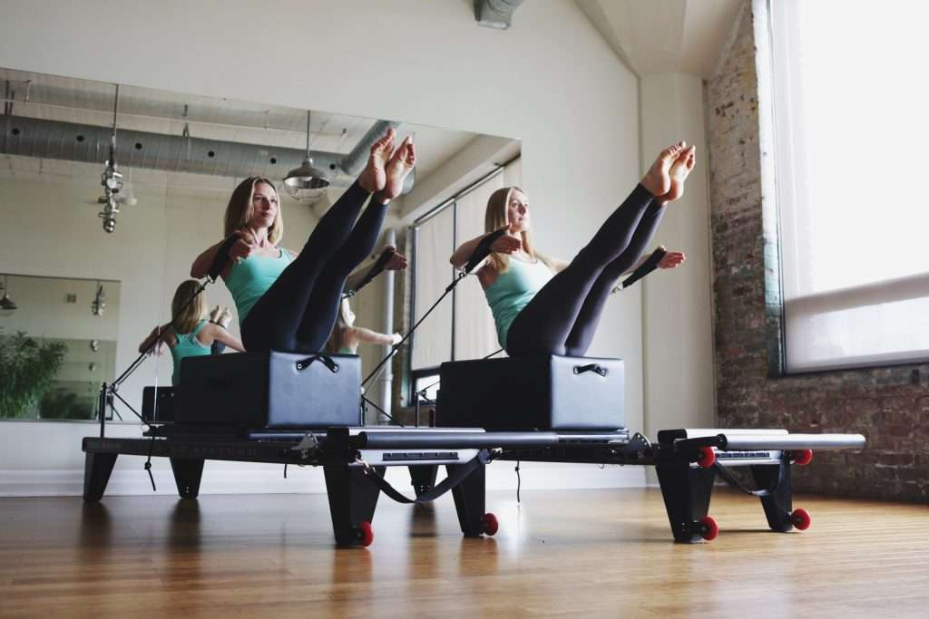 Two attractive, athletic girls doing Pilates on the Reformer